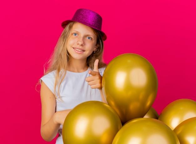 Wesoła ładna mała dziewczynka w świątecznym kapeluszu z bukietem balonów, uśmiechnięta, wskazująca palcem wskazującym na aparat, koncepcja przyjęcia urodzinowego stojącego na różowym tle