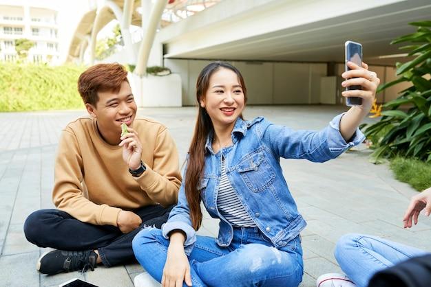 Wesoła, ładna młoda azjatka robi selfie lub nagrywa wideo ze swoją przyjaciółką