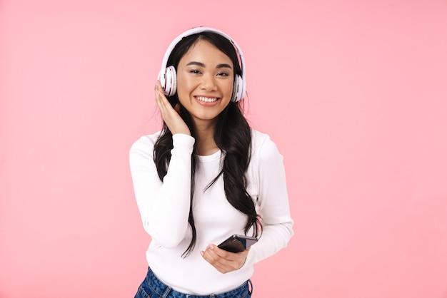 Wesoła ładna młoda azjatycka kobieta słuchająca muzyki przez bezprzewodowe słuchawki na białym tle, trzymająca telefon komórkowy