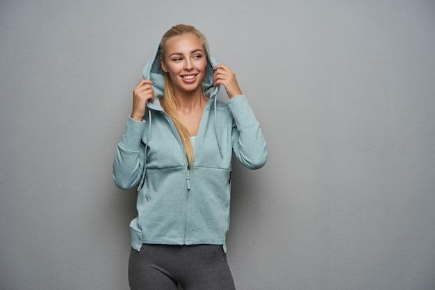 Wesoła, ładna młoda blondynka, długowłosa kobieta ubrana w strój sportowy, stojąca na jasnoszarym tle, zakładająca kaptur i patrząc radośnie na bok z szerokim uśmiechem