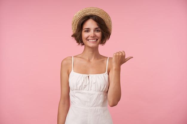 Wesoła ładna młoda brunetka kobieta z przypadkową fryzurą wskazującą na bok z podniesionym kciukiem, patrząc szczęśliwie, odizolowana w białej eleganckiej sukience i kapeluszu