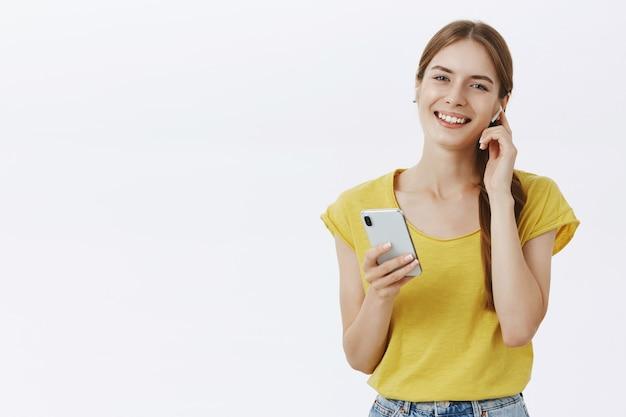 Wesoła ładna młoda dziewczyna słuchania muzyki w słuchawkach bezprzewodowych, trzymając smartfon, ciesząc się podcastem