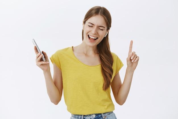 Wesoła ładna młoda dziewczyna słuchania muzyki w słuchawkach bezprzewodowych, trzymając smartfon i taniec