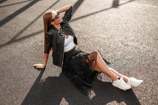 Wesoła ładna młoda hipster kobieta w modnych ciuchach w stylowych okularach przeciwsłonecznych siedzi na chodniku i cieszy się jesiennym słońcem. atrakcyjna szczęśliwa dziewczyna z ślicznym uśmiechem odpoczywa na świeżym powietrzu.