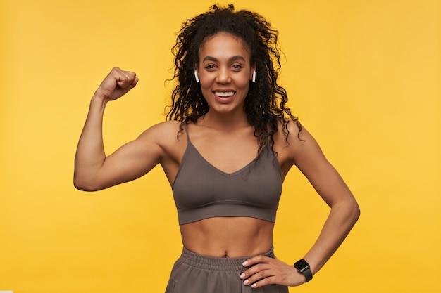 Wesoła, ładna młoda kobieta fitness, korzystająca z bezprzewodowych słuchawek i inteligentnego zegarka, pokazująca mięśnie bicepsa odizolowane nad żółtą ścianą