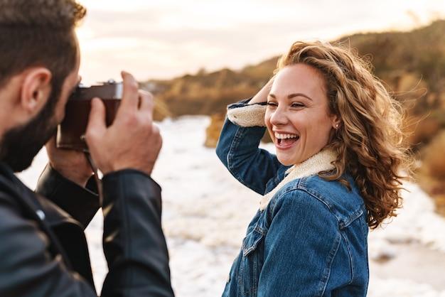 Wesoła ładna młoda kobieta pozuje przed swoim chłopakiem, który zabiera ją na plażę