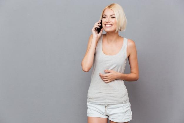 Wesoła ładna młoda kobieta rozmawia przez telefon komórkowy przez szarą ścianę