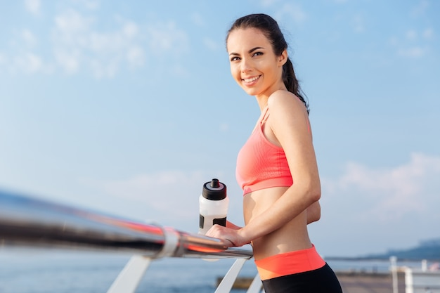 Wesoła, ładna młoda kobieta sportowiec z butelką wody stojącą i uśmiechającą się na molo