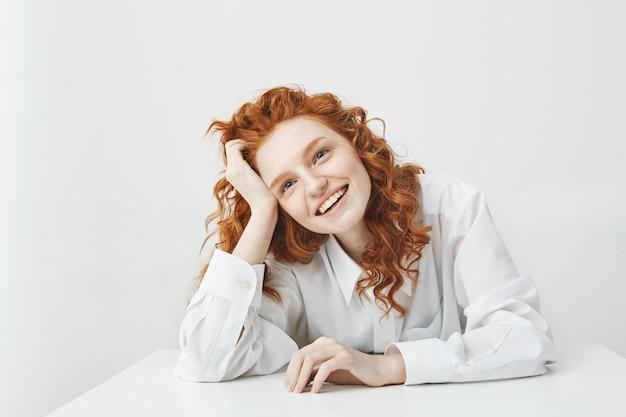 Wesoła ładna młoda kobieta z czerwonymi włosami, uśmiechając się, śmiejąc się, siedząc przy stole na białej ścianie