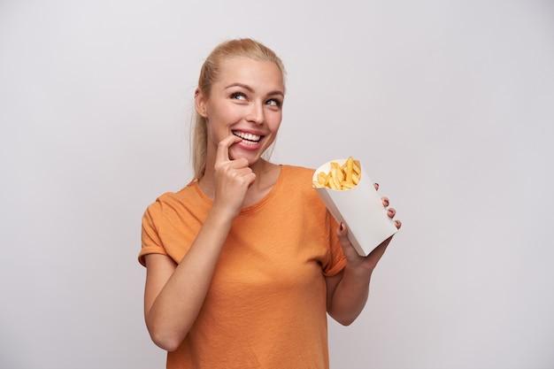 Wesoła ładna niebieskooka młoda blondynka trzyma papierowe pudełko z frytkami i patrzy w górę w zamyśleniu z szerokim uśmiechem, licząc kalorie w głowie, odizolowana na białym tle