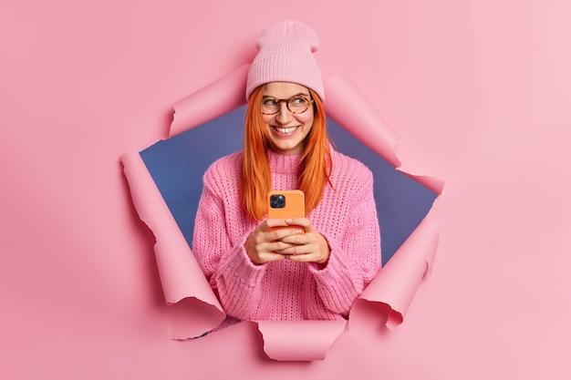 Wesoła ładna rudowłosa modelka używa telefonu komórkowego do komunikacji online, uśmiecha się radośnie czyta otrzymane wiadomości na czacie o planach weekendowych, nosi ciepły sweter z dzianiny i czapkę.