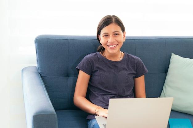 Wesoła latynoska studentka śmiejąca się z laptopem w domu