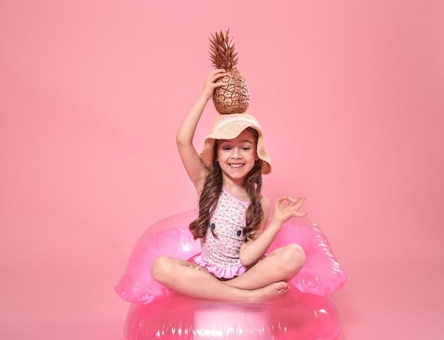 Wesoła letnia dziewczyna z ananasem na kolorowym tle