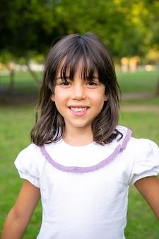 Wesoła mała czarnowłosa dziewczyna stojąca w parku miejskim. dzieciak korzystający z wolnego czasu na świeżym powietrzu latem. średni strzał, pionowy. koncepcja dzieciństwa