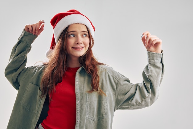Wesoła mała dziewczynka w czerwonym kapeluszu, gestykuluje rękami, zabawa tańczy boże narodzenie nowy rok. wysokiej jakości zdjęcie