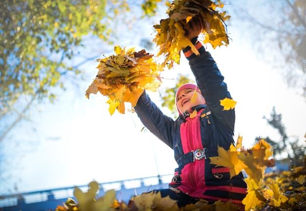 Wesoła mała kobieta trzyma żółte liście klonu