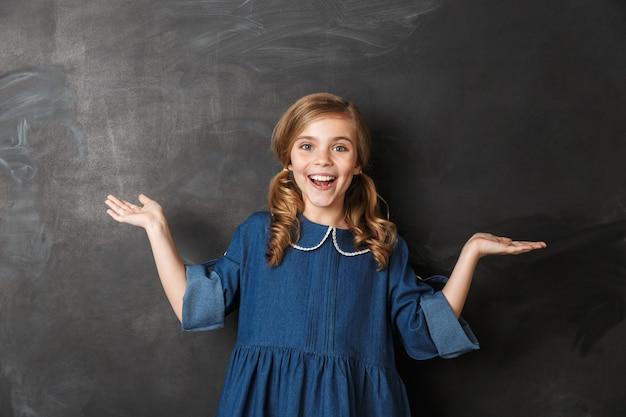 Wesoła mała uczennica stojąca przy tablicy