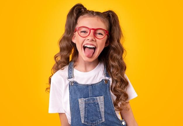 Wesoła mała uczennica z kręconymi kucykami, ubrana w modny dżinsowy kombinezon i okulary, bawi się i pokazuje język