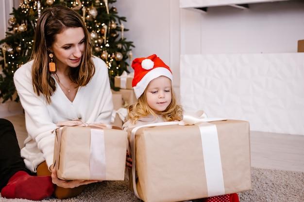 Wesoła mama daje świąteczny prezent swojej uroczej córce. rodzic i małe dziecko, zabawy w pobliżu drzewa w pomieszczeniu.