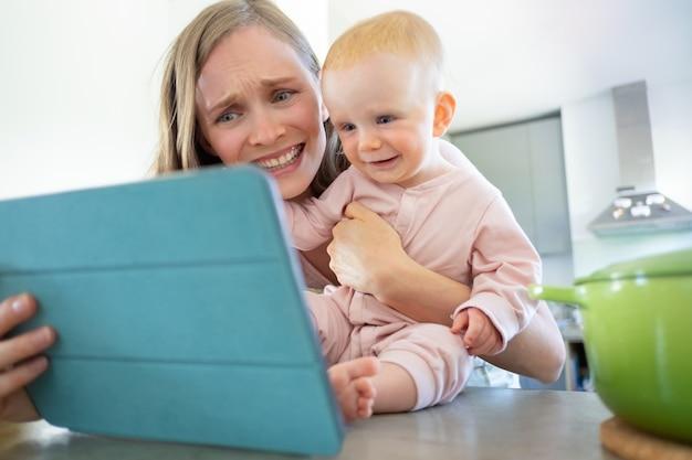 Wesoła mama i córeczka śmieją się z ekranu tabletu, oglądają seminarium online lub rozmawiają wideo. opieka nad dziećmi lub gotowanie w domu koncepcja
