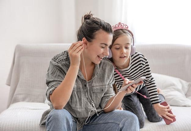 Wesoła mama i córka odpoczywają w domu, słuchając muzyki na słuchawkach