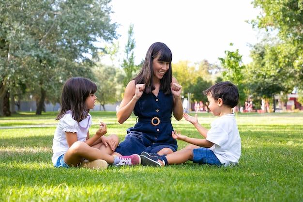 Wesoła mama i dwoje dzieci siedzi na trawie w parku i gra. szczęśliwa mama i dzieci spędzają wolny czas latem. koncepcja rodziny na zewnątrz