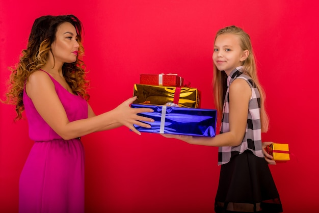 Wesoła mama i jej śliczna córka dziewczyna trzyma prezent. czerwone tło