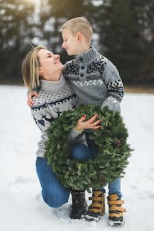 Wesoła mama i jej syn w szarych dzianinowych swetrach trzymają domowy wieniec adwentowy