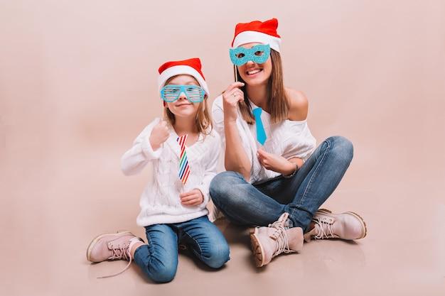 Wesoła mama i jej urocza szczęśliwa córka w karnawałowych maskach i czapkach mikołaja