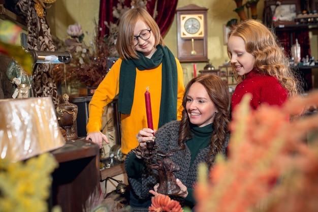 Wesoła mama rodzinna i dzieci szukające dekoracji domu i prezentów świątecznych w sklepie domowym