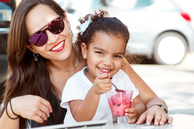 Wesoła matka i córka jedzenie lodów w parku