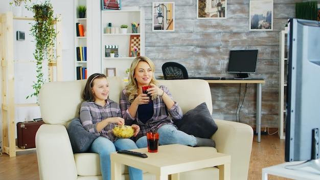 Wesoła matka i córka siedzi na kanapie w salonie oglądając telewizję, jedząc frytki i pijąc napoje gazowane.