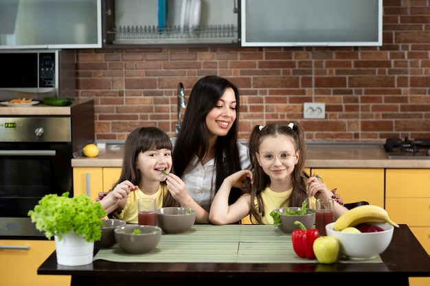 Wesoła matka i dwie córki jedzą razem zdrową sałatkę w domu. pojęcie zdrowego odżywiania, wartości rodzinne, czas razem