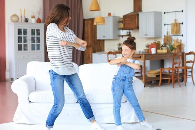 Wesoła matka z córeczką tańczy przy ulubionej piosence w salonie w domu.