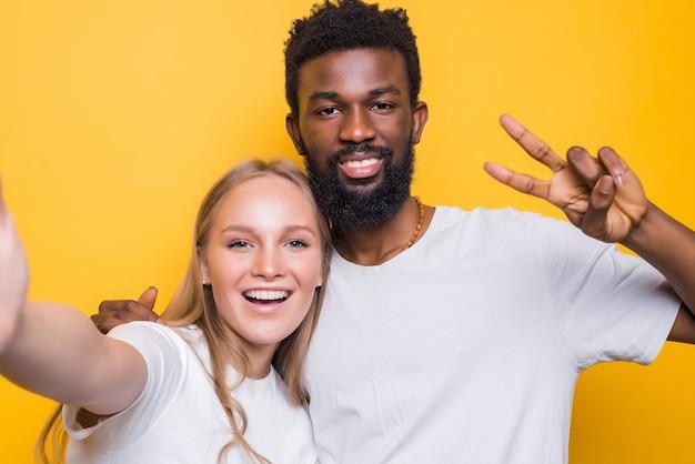 Wesoła międzyracjonalna para robiąca razem autoportret, patrząca z przodu i uśmiechnięta, pozująca na żółtej ścianie