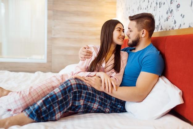 Wesoła miłość para w piżamie przytula się w łóżku w domu, dzień dobry. harmonijny związek w młodej rodzinie