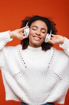 Wesoła młoda afrykańska kobieta słucha muzyki z bezprzewodowymi słuchawkami izolowanymi na czerwonej ścianie, tańczy