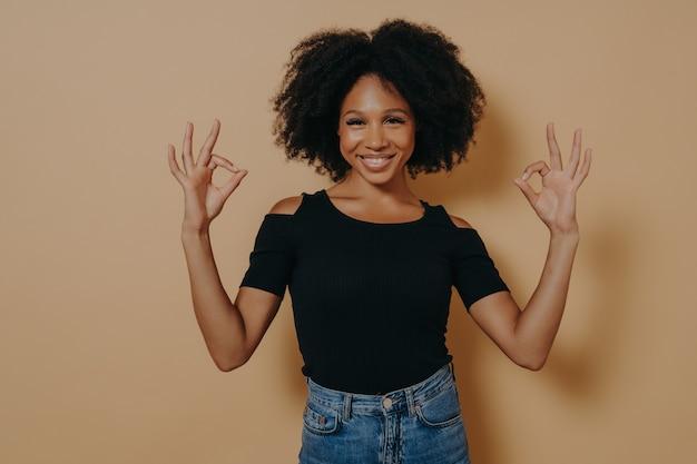 Wesoła młoda afrykańska kobieta ubrana w czarną koszulkę pokazuje ok znak, dobrze gest obiema rękami i demonstruje aprobatę, odizolowana na beżowym tle, uśmiechając się do kamery i mówiąc wszystko w porządku