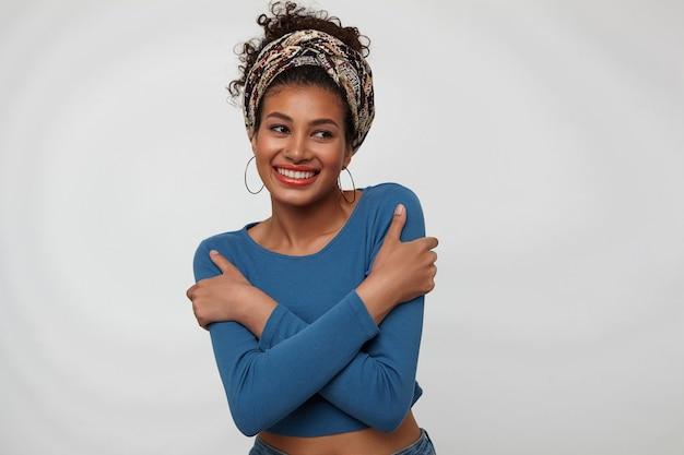 Wesoła młoda atrakcyjna brunetka kobieta z kolorowym pałąkiem przytulanie się z uniesionymi rękami i uśmiechając się radośnie stojąc na białym tle