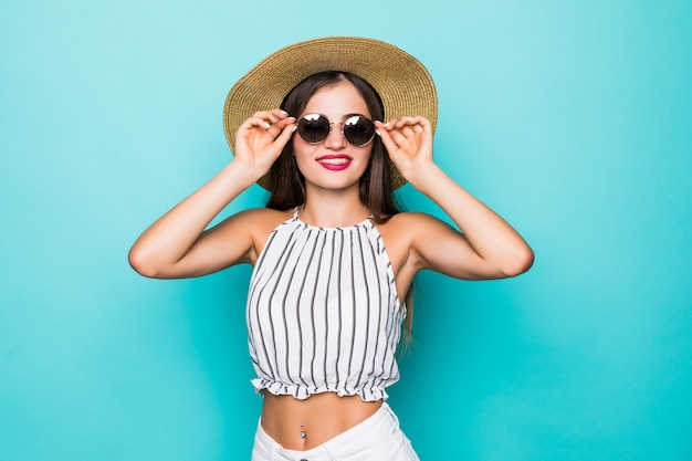 Wesoła młoda atrakcyjna kobieta w okulary i kapelusz na turkusowym tle