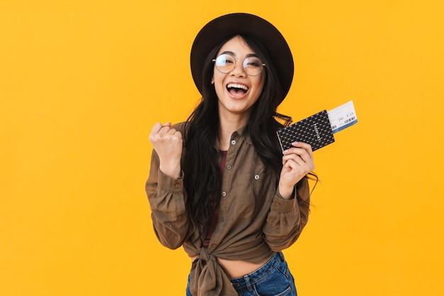 Wesoła młoda azjatycka kobieta pokazuje paszport z biletami lotniczymi na białym tle, świętuje