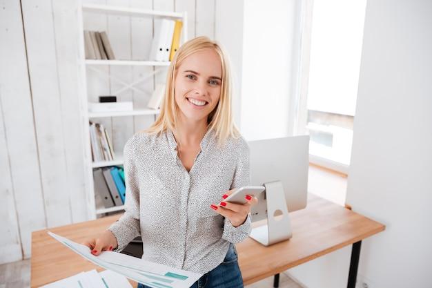 Wesoła młoda biznesowa kobieta korzystająca z telefonu komórkowego, stojąc w swoim miejscu pracy