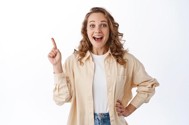 Wesoła młoda blond dziewczyna z kręconymi włosami, stylowe ubrania, palcem wskazującym w lewym górnym rogu, pokazująca ofertę promocyjną, stojąca nad białą ścianą