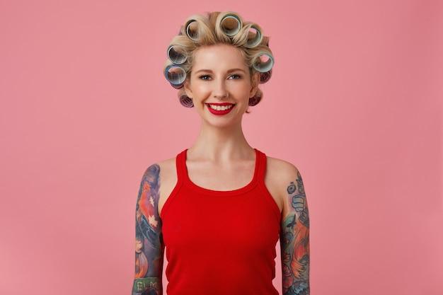 Wesoła młoda blondynka wytatuowana kobieta z wieczorowym makijażem robi fryzurę, pozując na różowym tle z opuszczonymi rękami, patrząc na kamerę z uroczym uśmiechem