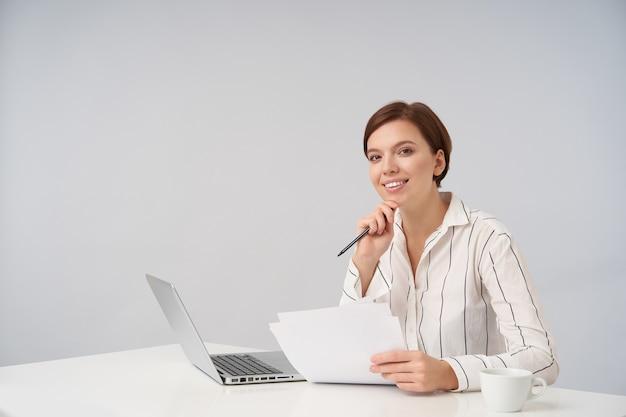 Wesoła młoda brązowooka krótkowłosa kobieta uśmiecha się przyjemnie i opiera brodę na uniesionej dłoni, pozuje na biało z laptopem i dokumentami