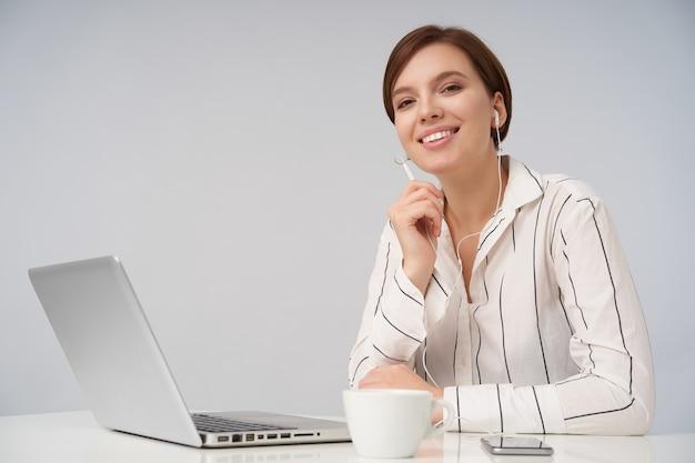 Wesoła młoda brązowooka krótkowłosa kobieta z naturalnym makijażem, uśmiechnięta szczerze, siedząca w biurze z laptopem i nawiązująca połączenie z zestawem słuchawkowym, na białym tle