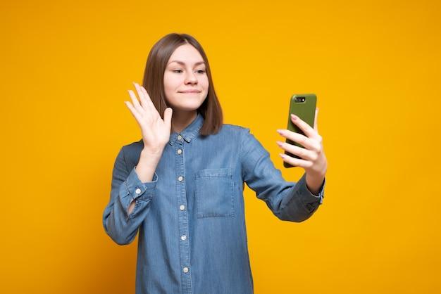 Wesoła młoda brunetka kobieta w pastelowej niebieskiej sukience pozowanie na telefon komórkowy