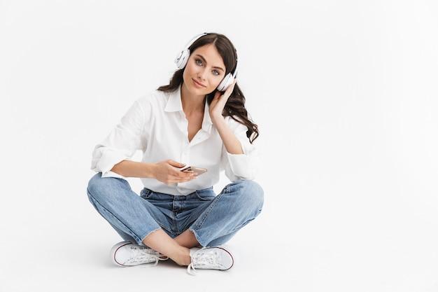 Wesoła młoda brunetka ubrana w koszulę siedząca na białym tle nad białą ścianą, słuchająca muzyki przez słuchawki i telefon komórkowy