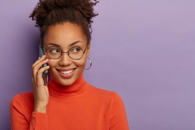 Wesoła młoda, ciemnoskóra kobieca dziewczyna rozmawia przez telefon komórkowy, nosi okrągłe przezroczyste okulary, ma czarujący uśmiech, słyszy dobre wieści, odizolowana na fioletowej ścianie studia, miejsce na kopię