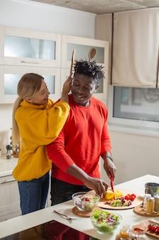 Wesoła młoda dama bawi się w kuchni i zakłada dwa drewniane uszy za głowę swojego chłopaka, udając, że robi uszy królika